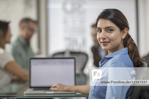 Portrait of smiling businesswoman with laptop during a meeting in office boardroom