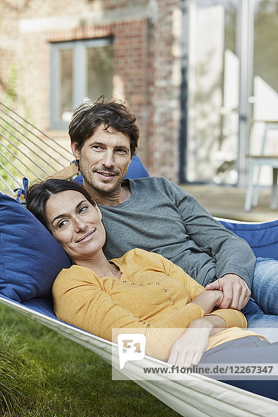 Smiling couple lying in hammock in garden of their home