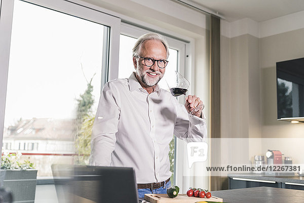 Porträt des lächelnden reifen Mannes in der Küche mit einem Glas Rotwein