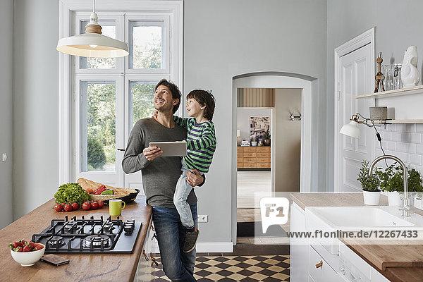 Vater und Sohn mit Tablette in der Küche mit Blick auf die Deckenlampe