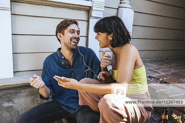 Glücklicher junger Mann und Frau mit Smartphone und Kopfhörer