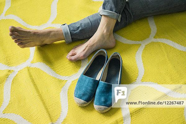 Füße und Schuhe einer Frau  entspannt auf einem gelben Teppich
