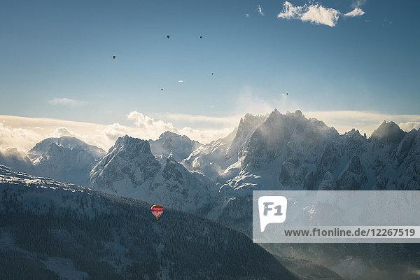 Österreich  Salzkammergut  Heißluftballons über alpiner Landschaft mit Gosaukamm im Winter