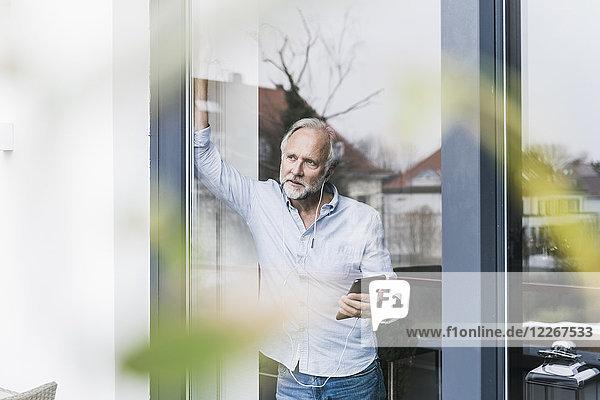 Erwachsener Mann hört Musik mit Kopfhörern und Phablet  das aus der Terrassentür schaut.