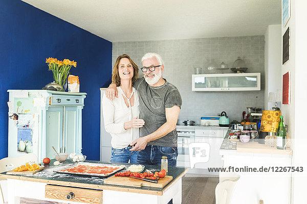 Glückliches reifes Paar  das sich in der Küche zu Hause umarmt.