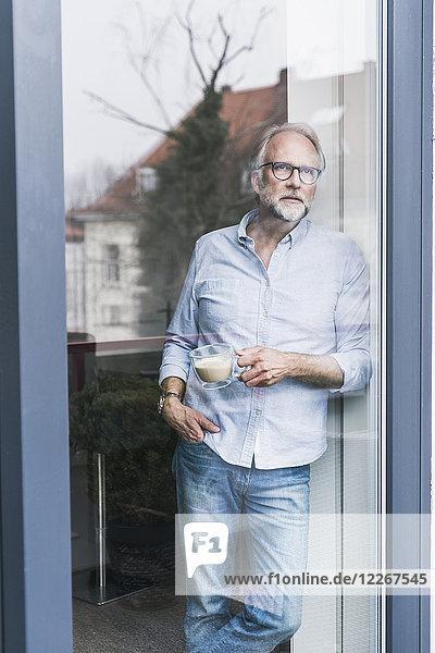 Porträt eines reifen Mannes mit Blick aus der Terrassentür