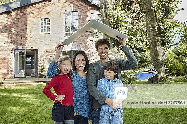 Porträt einer glücklichen Familie im Garten ihres Hausdaches