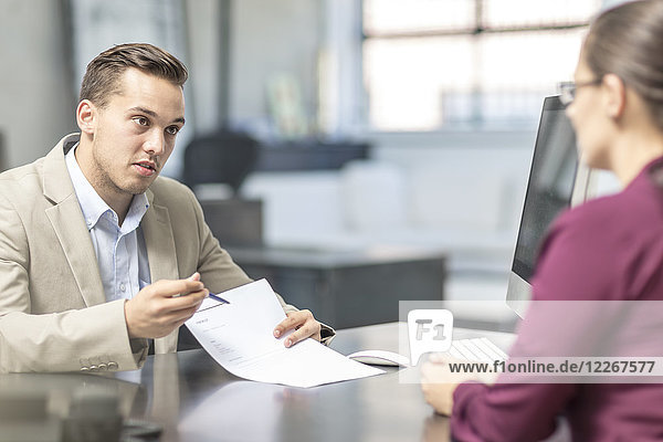 Man showing document to woman at desk