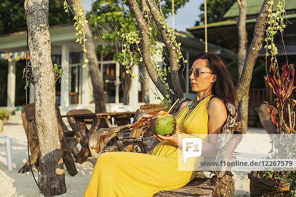 Thailand  Koh Phangan  Frau sitzt in einem Strandcafé und trinkt Kokoswasser.