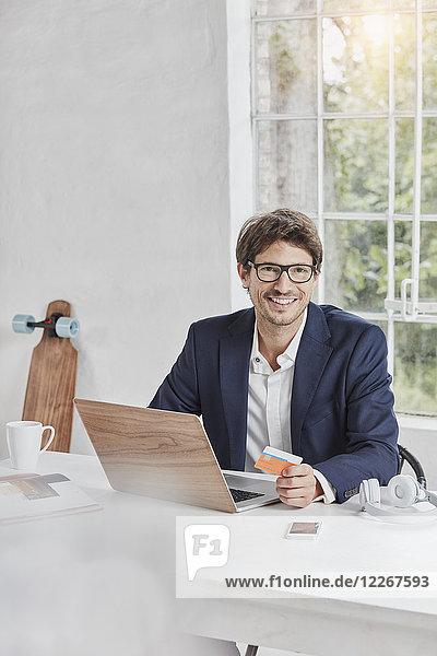 Porträt eines lächelnden Geschäftsmannes mit Laptop auf Schreibtisch-Haltekarte