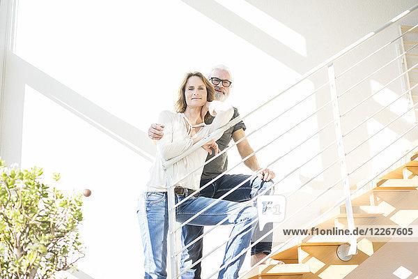 Porträt eines lächelnden  reifen Paares  das zu Hause auf einer Treppe steht.