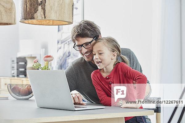 Glücklicher Vater und Tochter mit Laptop auf dem Tisch zu Hause
