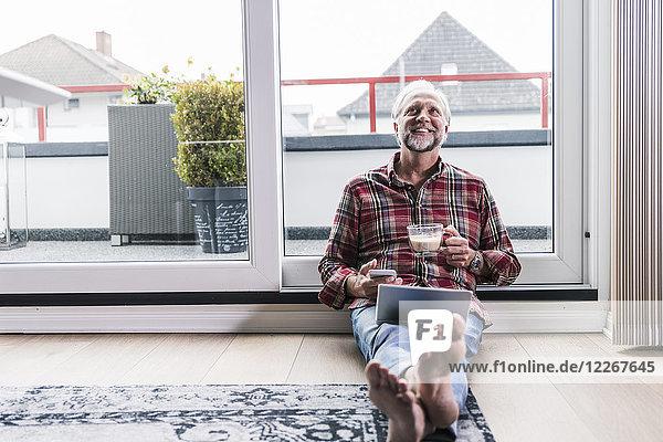 Fröhlicher Mann  der sich zu Hause mit Laptop  Handy und einer Tasse weißem Kaffee auf dem Boden entspannt