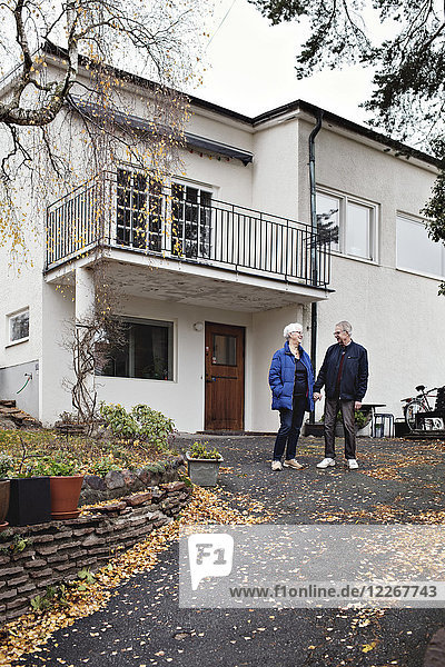 Volle Länge des lächelnden Rentnerpaares  das gegen Haus steht