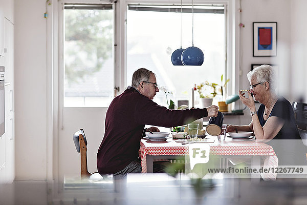 Side view of senior couple eating food at dining table against window