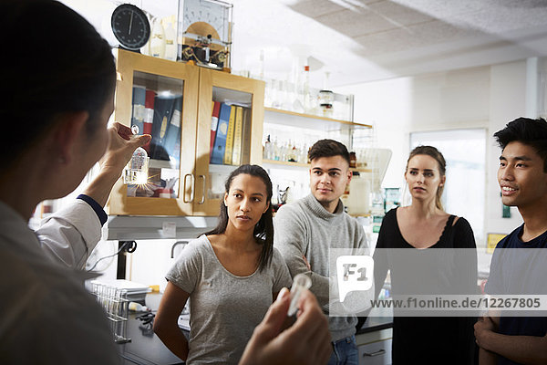 Rear view of mature female teacher showing solution while explaining to young multi-ethnic students in laboratory