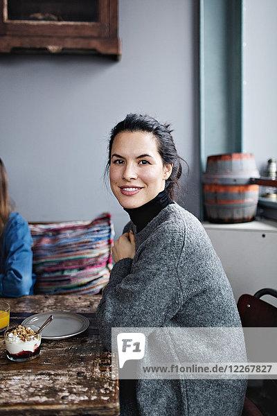 Porträt einer lächelnden Frau beim Brunch am Tisch