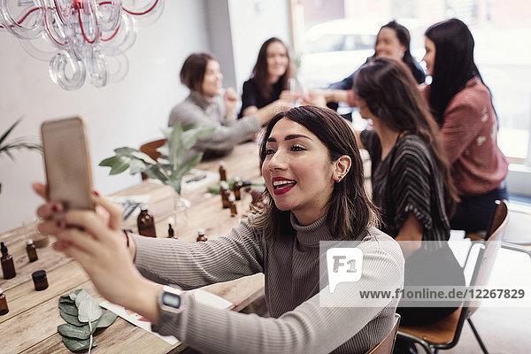 Lächelnde junge Frau nimmt Selfie mit weiblichen Kollegen am Tisch in der Parfümwerkstatt.