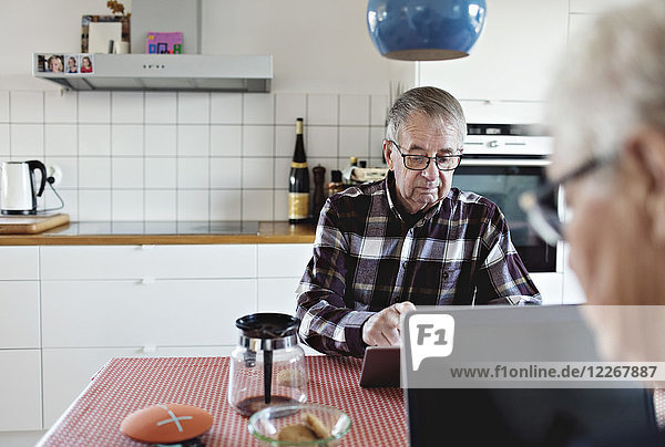 Senior couple using technologies sitting at dining table