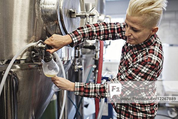 Zuverlässige Managerin schüttet Bier aus Lagertank in der Fabrik aus