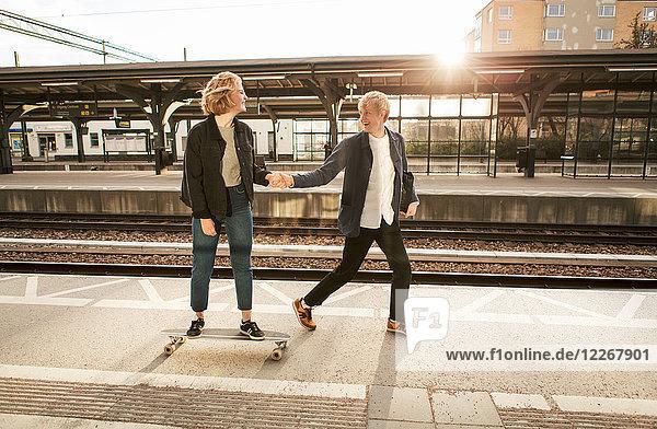Fröhlicher junger Mann zieht Teenager-Mädchen auf Skateboard am Bahnsteig des Bahnhofs