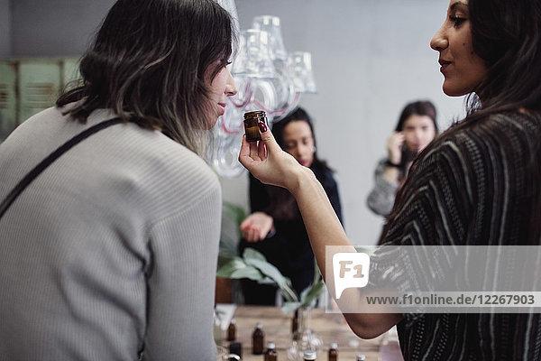 Rückansicht einer jungen Frau  die eine Flasche hält  während ein Kollege in der Werkstatt Parfüm riecht.