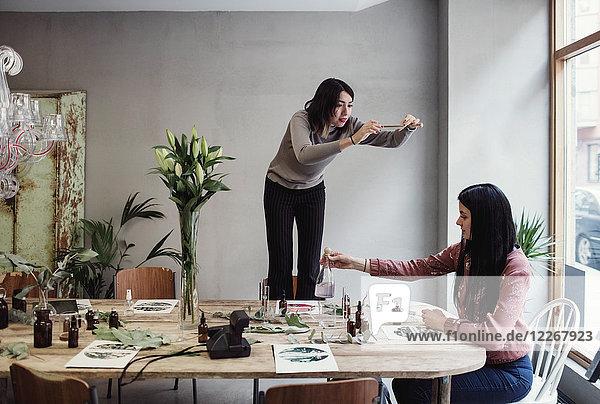 Junge Frau beim Fotografieren  während die Kollegin am Tisch in der Werkstatt Parfüm zubereitet.