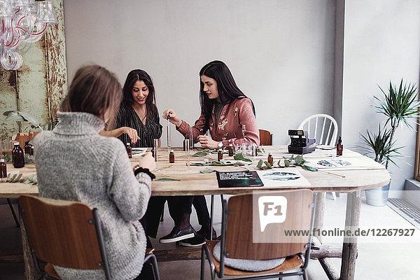 Weibliche Kollegen bei der Parfumzubereitung am Tisch in der Werkstatt