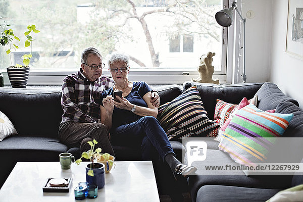 Seniorenpaar teilt sich ein Smartphone auf dem Sofa im Wohnzimmer gegen das Fenster zu Hause.