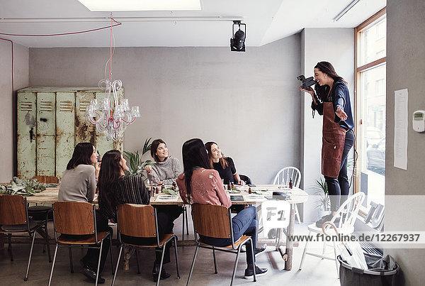 Fröhliche Frau auf dem Stuhl stehend  die weibliche Kollegen am Tisch in der Werkstatt fotografiert.