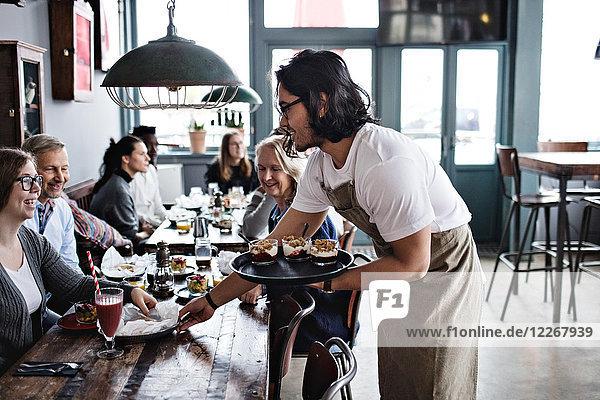 Kellner serviert Speisen für lächelnde Kunden im Restaurant