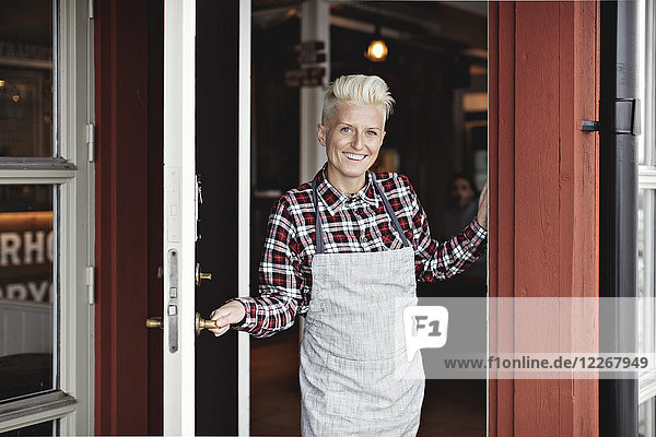 Portrait of smiling confident manual worker standing at doorway by restaurant