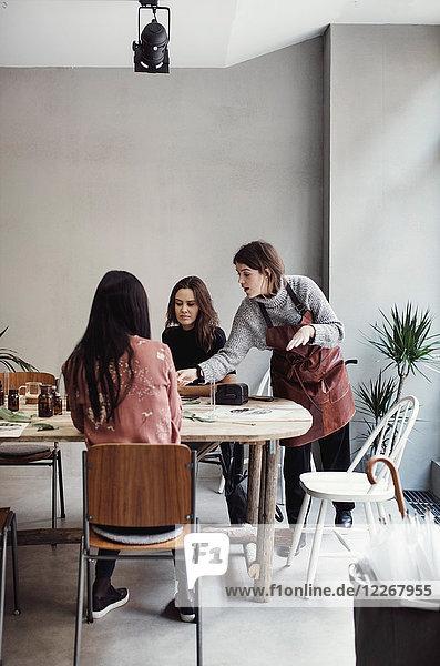 Selbstbewusste Inhaberin unterrichtet Kollegen am Tisch in der Parfümwerkstatt