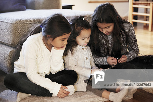 Sisters watching digital tablet while sitting on carpet at home