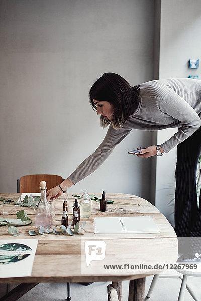 Volle Länge der jungen Frau  die auf dem Stuhl steht und den Tisch in der Parfumwerkstatt arrangiert.