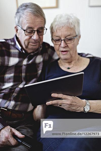 Seniorenpaar  das sich zu Hause ein digitales Tablett gegen die Wand teilt.