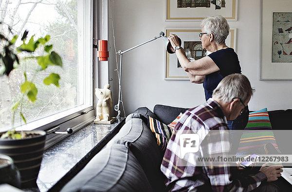 Seniorin mit Stehleuchte von Mann auf Sofa sitzend im Wohnzimmer zu Hause
