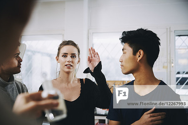 Junge Studentin steht mit erhobener Hand inmitten von Männern und schaut auf die Lehrerin im Chemielabor.