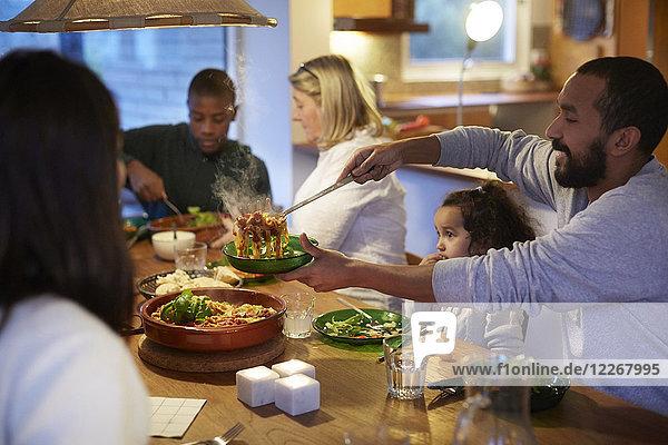 Vater serviert Essen  während er mit der Familie am Tisch sitzt.
