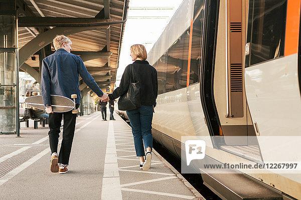 Rückansicht eines jungen Paares  das beim Gehen mit dem Zug am Bahnsteig Händchen hält.