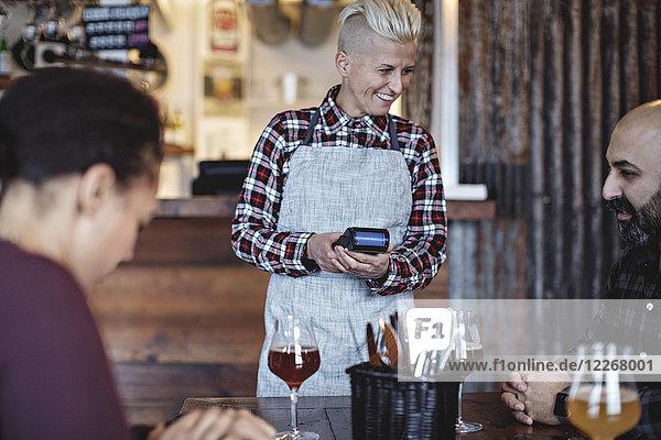 Lächelnde Barkeeperin mit Kreditkartenleser im Gespräch mit Kunden am Tisch in der Bar