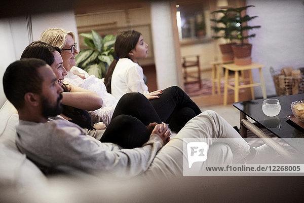 Familie beim Fernsehen auf dem Sofa im heimischen Wohnzimmer