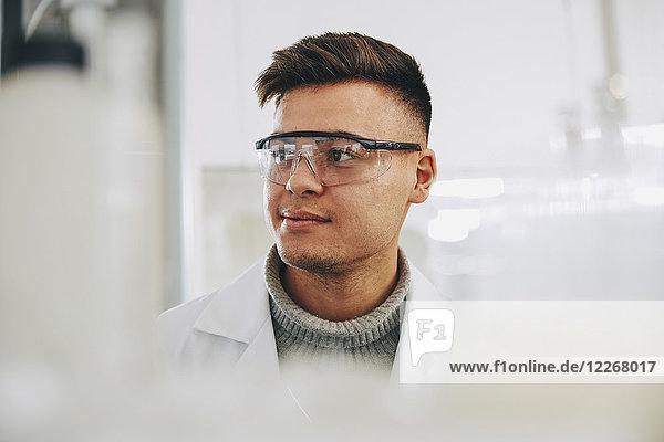Zuversichtlicher junger Chemiestudent mit Brille im Labor