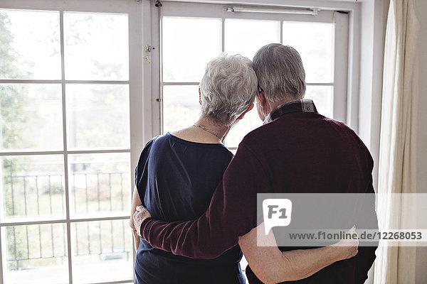 Rückansicht des Rentnerpaares beim Blick durchs Fenster zu Hause