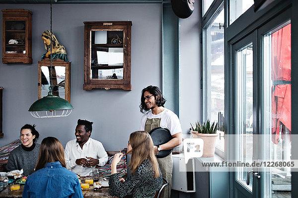 Lächelnder Besitzer im Gespräch mit jungen Männern und Frauen am Esstisch im Restaurant