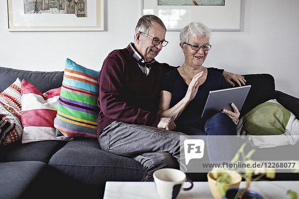 Lächelndes Seniorenpaar sitzt auf dem Sofa und teilt sich ein digitales Tablett im Wohnzimmer zu Hause.
