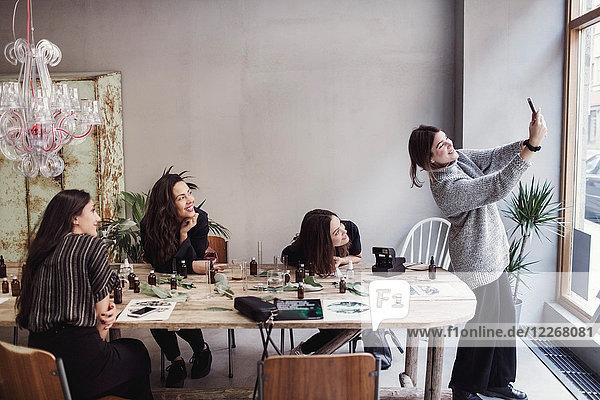 Lächelnde Besitzerin nimmt Selfie mit weiblichen Mitarbeitern am Tisch in der Parfümwerkstatt auf