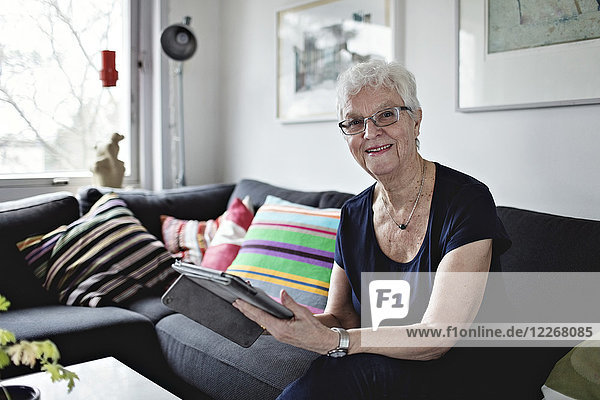 Portrait of confident senior woman sitting with digital tablet on sofa in living room at home