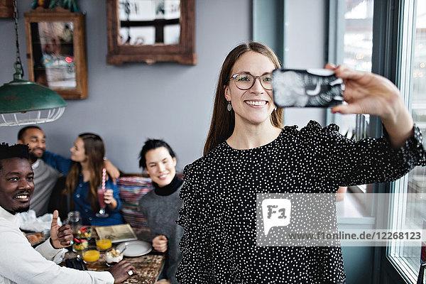 Lächelnde junge Frau nimmt Selfie mit Freunden im Restaurant mit.