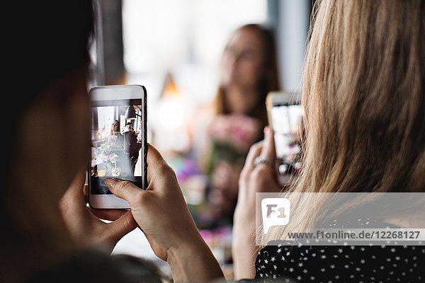 Frauen fotografieren Freund durch Smartphones am Esstisch im Restaurant